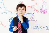 Child prodigy in meditations at chalkboard — Stock Photo