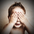 Portrait of little boy closed eyes with his hands — Stock Photo
