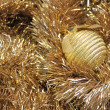 Golden christmas ball on a golden tinsel — Stock Photo