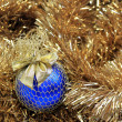 Foto Stock: Blue christmas ball on a golden tinsel