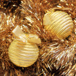 Golden christmas balls on a golden tinsel — Stockfoto