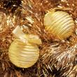 Golden christmas balls on a golden tinsel — Stock Photo