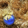 Blue christmas ball on a golden tinsel - Stock Photo