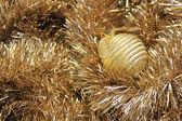 Bola de Natal ouro sobre um enfeites dourados — Fotografia Stock