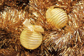 Golden christmas balls on a golden tinsel — Stock Photo