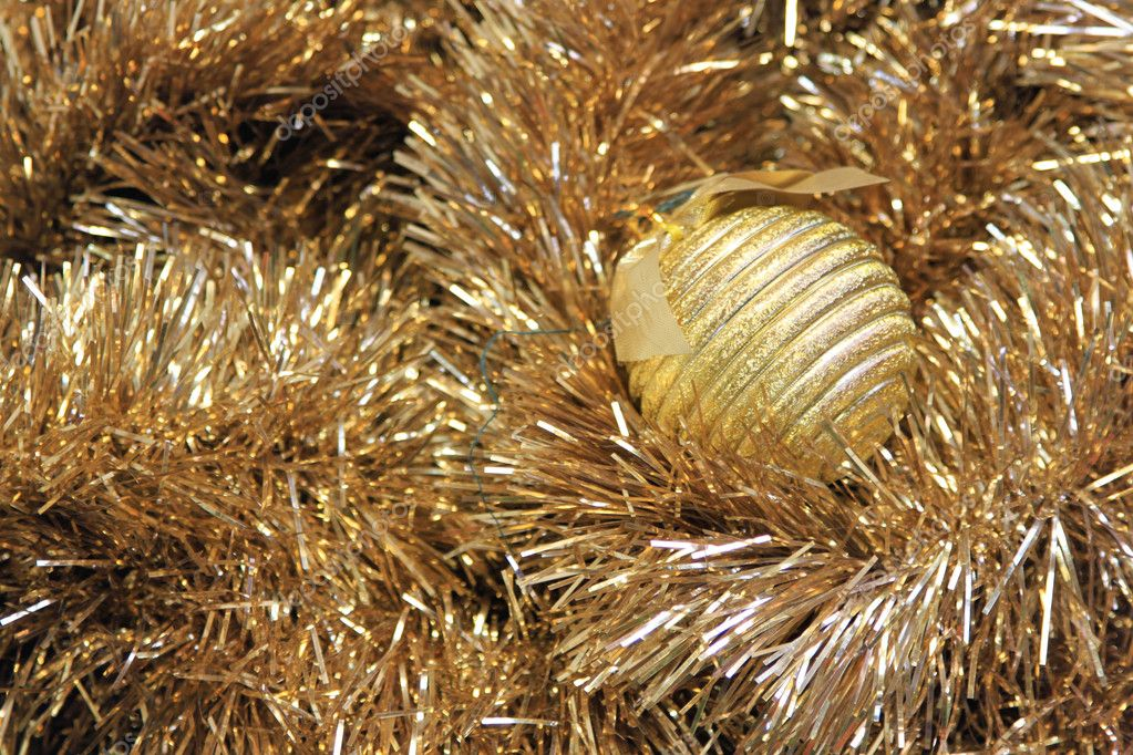 Golden christmas ball on a golden tinsel — Stock Photo #9250551