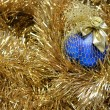 Photo: Blue christmas ball on a golden tinsel