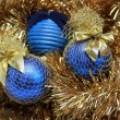 Blue christmas balls on a golden tinsel - Stock Photo