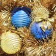 Foto Stock: Blue and golden christmas balls on a golden tinsel