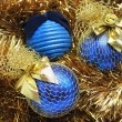 Blue christmas balls on a golden tinsel — Stok fotoğraf