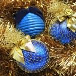 Blue christmas balls on a golden tinsel — Stock Photo