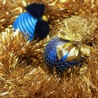 Foto Stock: Blue christmass balls on a golden tinsel