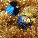 Blue christmass balls on a golden tinsel — Stock Photo