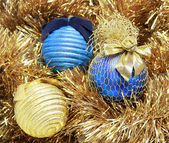 Blue and golden christmas balls on a golden tinsel — Stock Photo
