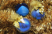 Blue christmas balls on a golden tinsel — Stock Photo