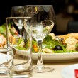 Glasses and plates on table in restaurant - food background — Stock Photo