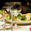 Glasses and plates on table in restaurant - food background — Stock Photo #10544079