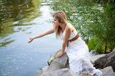 Young cute girl near the river — Stock Photo