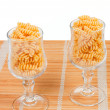 Macaroniin a glass on a straw mat - Stock Photo