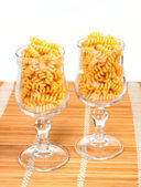 Macaroniin a glass on a straw mat — Stock Photo