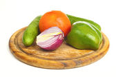 Pepper, onion, cucumber and tomato on a desk — Stock Photo