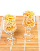 Macaroni in a glass on a straw mat — Stock Photo
