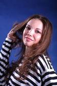 Morena jovencita posando sobre fondo azul — Foto de Stock