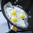 Broken egg frying in a pan - Stockfoto