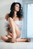 Vacker kvinna sitter vid ett fönster — Stockfoto