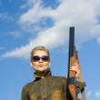 Blonde girl in sunglasses holding hunter rifle. — Stock Photo