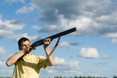 Caucasian man aiming. Cloudy sky background. — Stock Photo