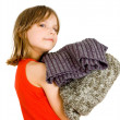 Little girl with stack of sweaters - Stock Photo