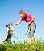 Woman with her dog on meadow — Stock Photo