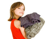 Little girl with stack of sweaters — Stock Photo