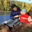 Two happy and smiling brothers sitting at lake in autumn park — Stok fotoğraf
