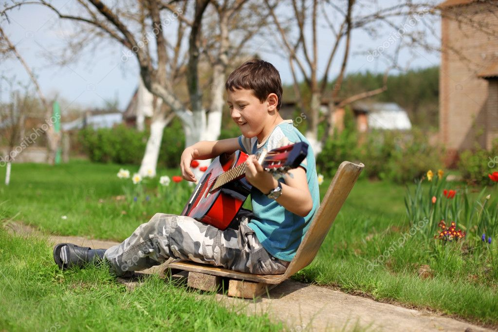 Music student playing the guitar outdoors  Stock Photo #10733514
