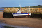 Small boat at ebb tide waiting for the rising water — Stock Photo