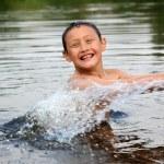 Boy in river with splash — Stock Photo #9409889