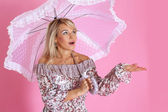Woman under umbrella against pink — Stock Photo