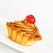 Cake with cherry on dish — Stock Photo