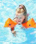 Child with armbands playing in swimming pool. — Stock fotografie