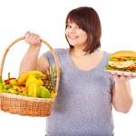 Woman choosing between fruit and hamburger. — Stock Photo #10526729