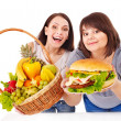 Women choosing between fruit and hamburger. — Stock Photo #10526732