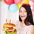 Woman eating hamburger at birthday. — Stock Photo
