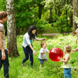 Outdoor happy family plaing ball . — Stock Photo