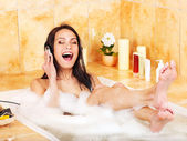 Woman listening to music in bubble bath. — Stock Photo