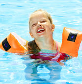 Child with armbands in swimming pool — Stock Photo
