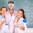 Stock Photo: Group chemistry student with flask.