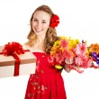 Young woman holding gift box and flowers. — Stock Photo #8633032