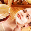 Stock Photo: Young woman having clay facial mask.